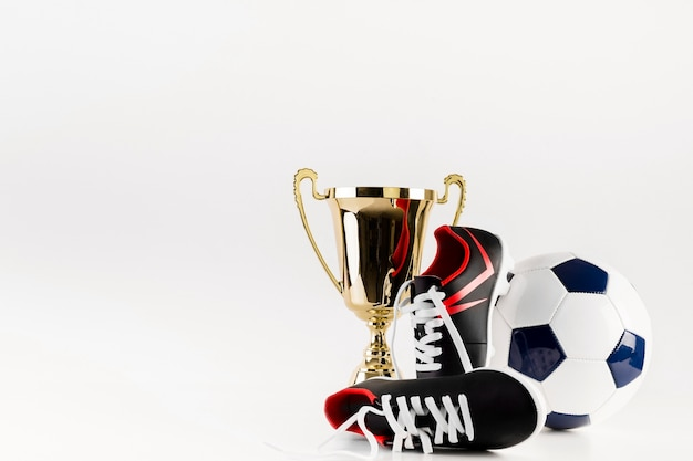 Football composition with shoes ball and trophy