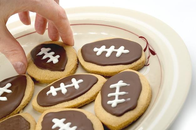 Футбольное печенье на тарелке, рука берет печенье с тарелки