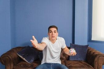 Football fan in disbelief on couch