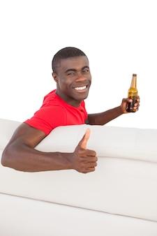 Футбольный болельщик в красном майке, сидя на диване с пивом, показывая пальцы вверх
