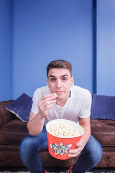 Football fan on couch with popcorn
