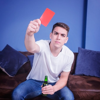 Football fan on couch with red card