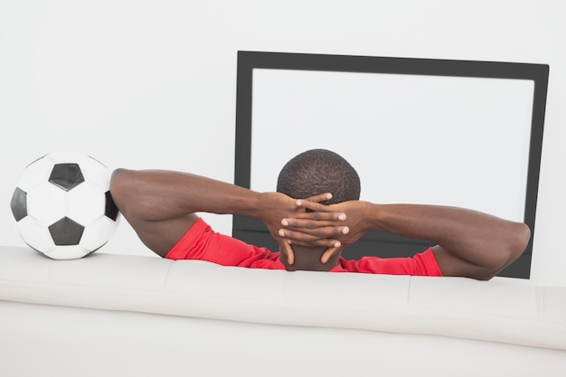 Football fan sitting on couch with ball