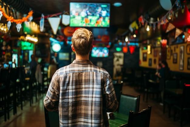 Футбольный болельщик смотрит матч в спорт-баре