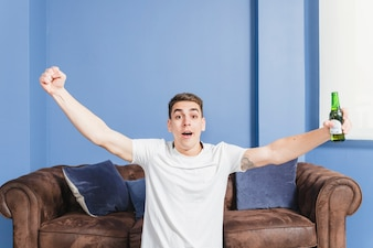 Football fan with beer in front of couch