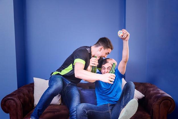 Gli appassionati di calcio festeggiano sul divano