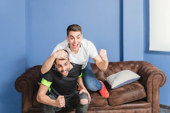 Football fans celebrating in living room