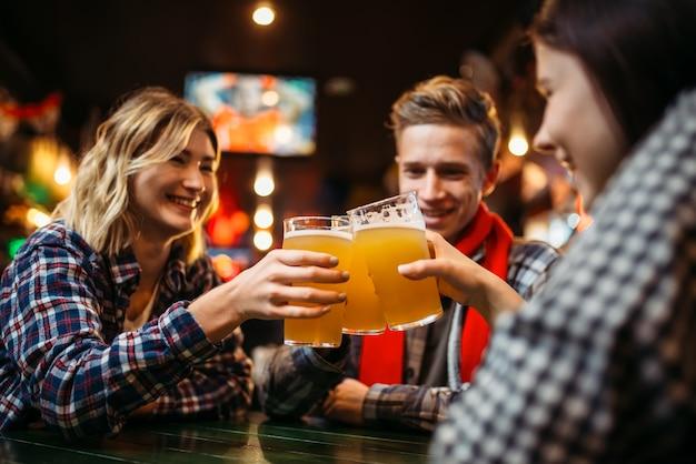 Любители футбола пьют пиво за столиком в спорт-баре. празднование победы, телетрансляция, отдых юных друзей в пабе