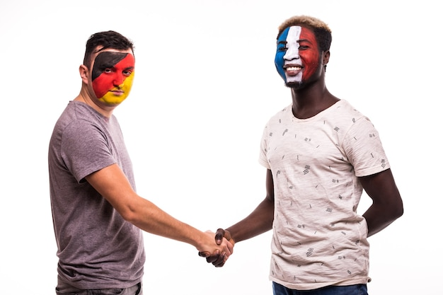 Football fans of germany and france national teams with painted face shake hands over white background