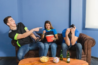 Football fans laughing in living room