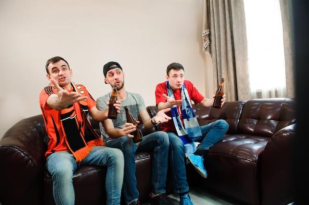 サッカーファン。男性はビールを飲み、チップを食べ、サッカーの根を張ります。