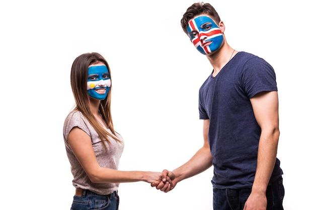 塗られた顔を持つアルゼンチンとアイスランドの代表チームのサッカーファンは、白い背景の上で握手します