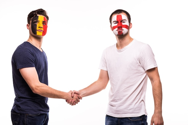 Футбольные болельщики сборных бельгии и англии с раскрашенным лицом пожимают друг другу руки на белом фоне