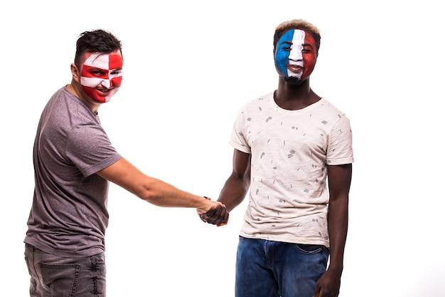 塗られた顔を持つクロアチアとフランスの代表チームのサッカーファンは、白い背景の上で握手します