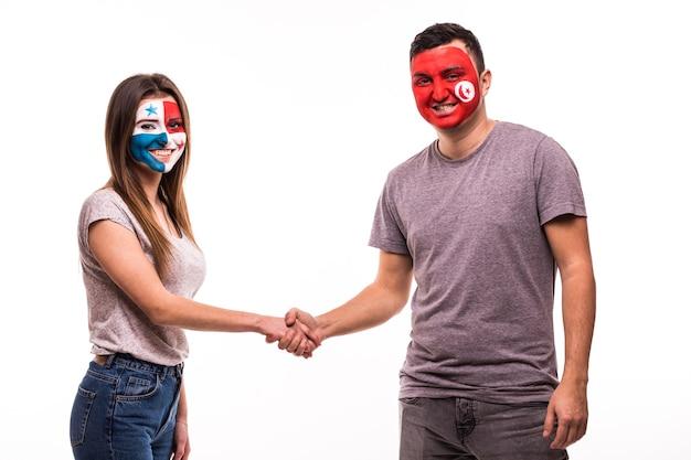 塗られた顔を持つパナマとチュニジアの代表チームのサッカーファンは、白い背景の上で握手します