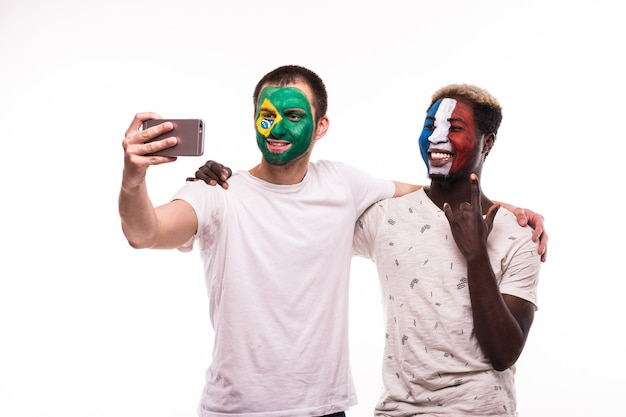 Football fans supporters with painted face of national teams of france and brazil take selfie isolated on white background