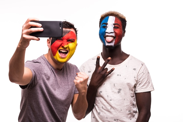 Football fans supporters with painted face of national teams of france and germany take selfie isolated on white background