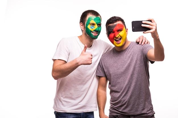 Сторонники футбольных фанатов с раскрашенными лицами сборных бразилии и германии делают селфи на белом фоне