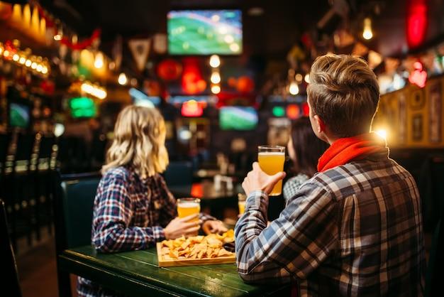 Футбольные фанаты смотрят матч и пьют пиво за столиком в спорт-баре.