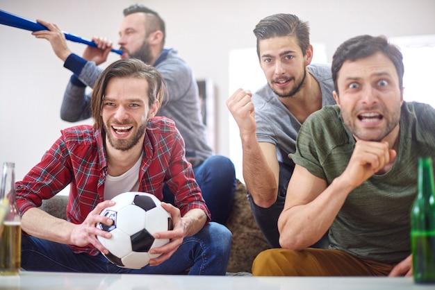 Футбольные болельщики смотрят матч дома