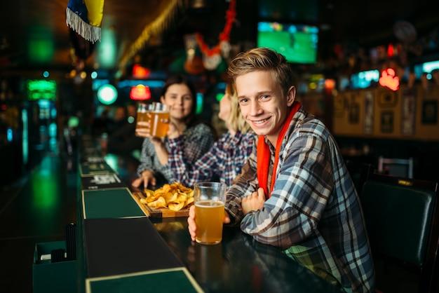スポーツバーのカウンターでビールのグラスを持つフットボールのファン。テレビ放送、若い友達が好きなチームの勝利を祝う、パブでの成功ゲームのお祝い