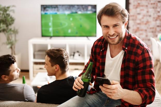 携帯電話とビールを持ったサッカーファン
