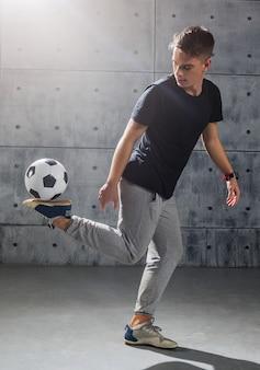 サッカーのフリースタイル。若い男はサッカーボールで練習します