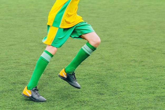 青少年チームのためのサッカーゲーム。子供たちはサッカーをしています。フィールドで選手を走らせます。サッカー選手がボールを蹴った。若いサッカー選手がボールを追いかけます。サッカースタジアム