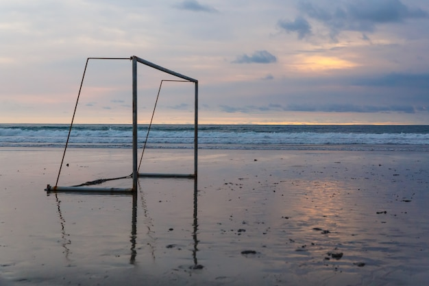 Футбольные ворота на берегу океана на закате.