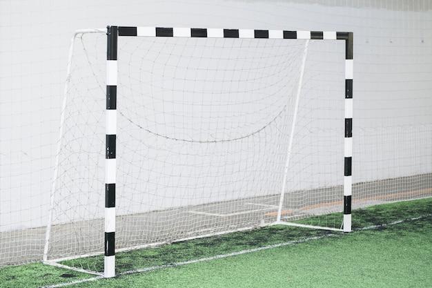 Футбольные ворота и сетка у белой стены на зеленом поле на стадионе для спортивных тренировок и матчей
