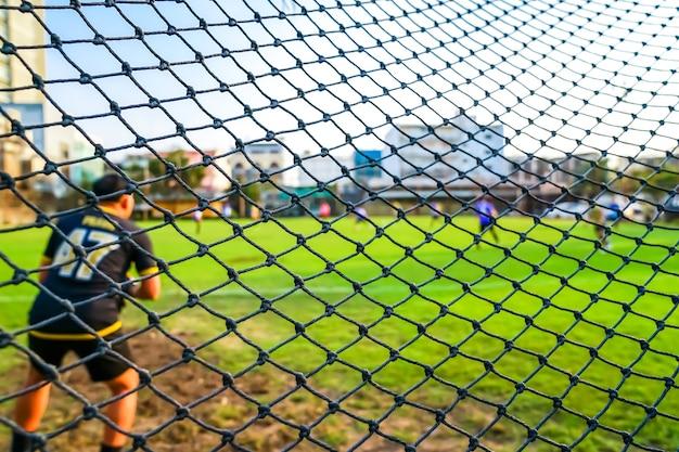 背景がぼやけているフィールドでのサッカーゴールネット。
