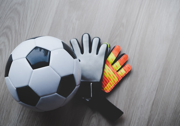 Football goalkeeper gloves with soccer ball top view on wooden Premium Photo