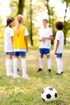 Футбол в траве рядом с детьми