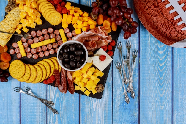 Football made from cheese and sausage for charcuterie board on wooden