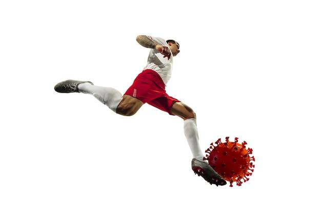 サッカー選手またはサッカー選手のキック、コロナウイルスのパンチングモデル-流行の概念との戦い。プロスポーツマン。エピデミックの蔓延、保護、生命と健康のための日常の闘争。