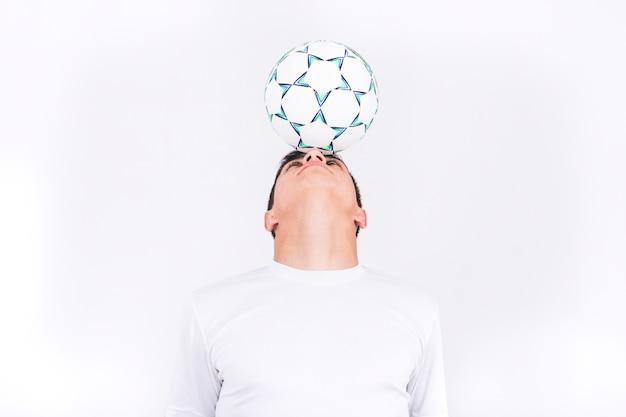 Football player balancing ball on head