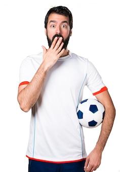 Футболист с футбольным мячом, делая неожиданный жест