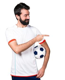 Футболист с футбольным мячом, указывающим на боковой