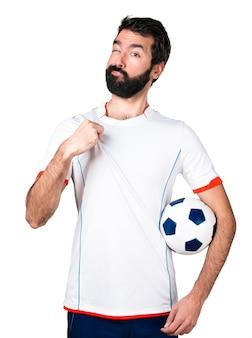 Футболист с футбольным мячом, гордящийся собой