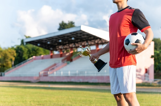 Football player holding champion trophy and soccer ball.