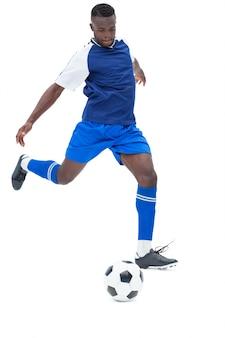 青い蹴りボールのサッカー選手
