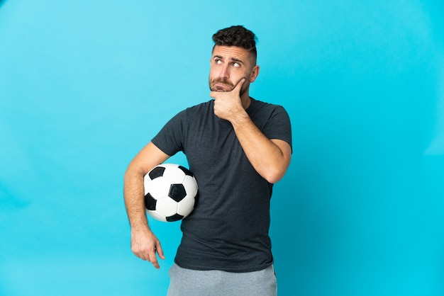 Football player isolated on blue background having doubts and thinking
