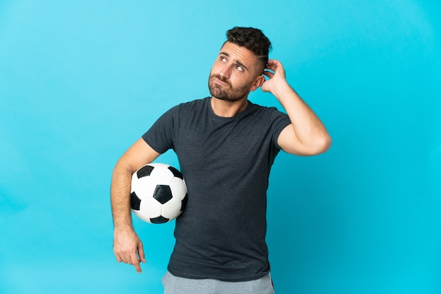 Football player isolated on blue background having doubts