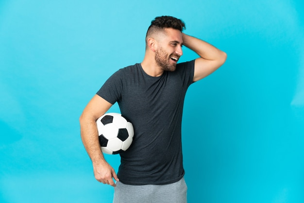 Football player isolated on blue background smiling a lot