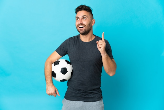 Football player isolated on blue background thinking an idea pointing the finger up