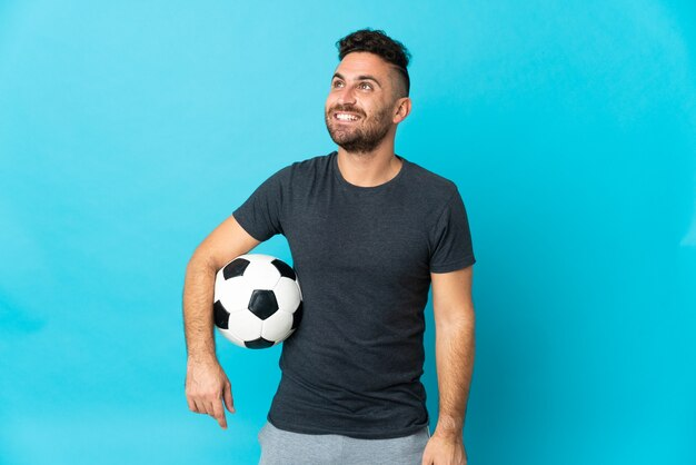 Football player isolated on blue background thinking an idea while looking up