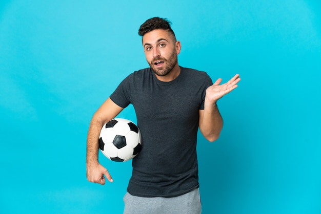 Football player isolated on blue background with shocked facial expression