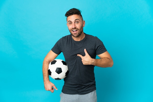 Football player isolated on blue wall with surprise facial expression