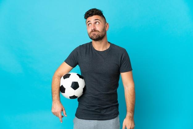 Футболист изолирован на синем фоне и смотрит вверх