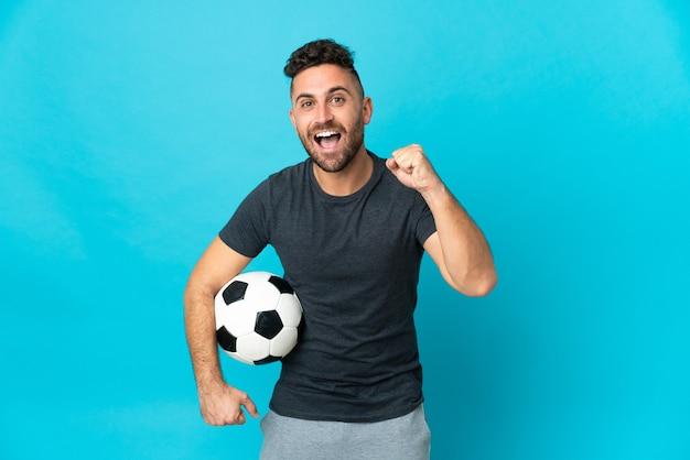 Футболист, изолированные на синем фоне, празднует победу в позиции победителя
